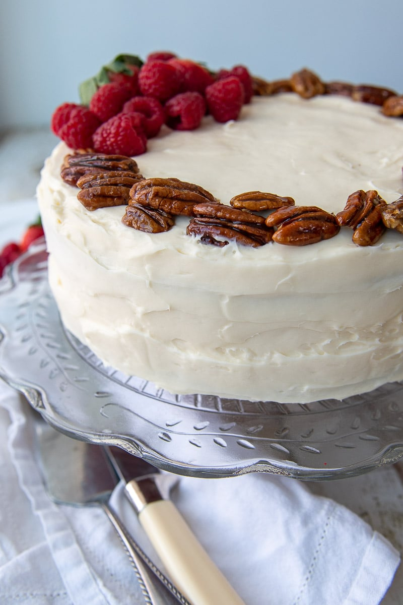 close up of cream cheese frosting and candied pecans on the layer cake