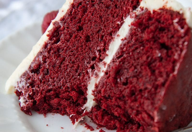 a slice of gluten free red velvet cake on a white plate with bites taken out