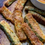 close up of baked zucchini fries on a baking sheet with dip in background