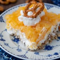 close up of a slice of pretzel salad with pineapple with whipped cream and pretzel on top