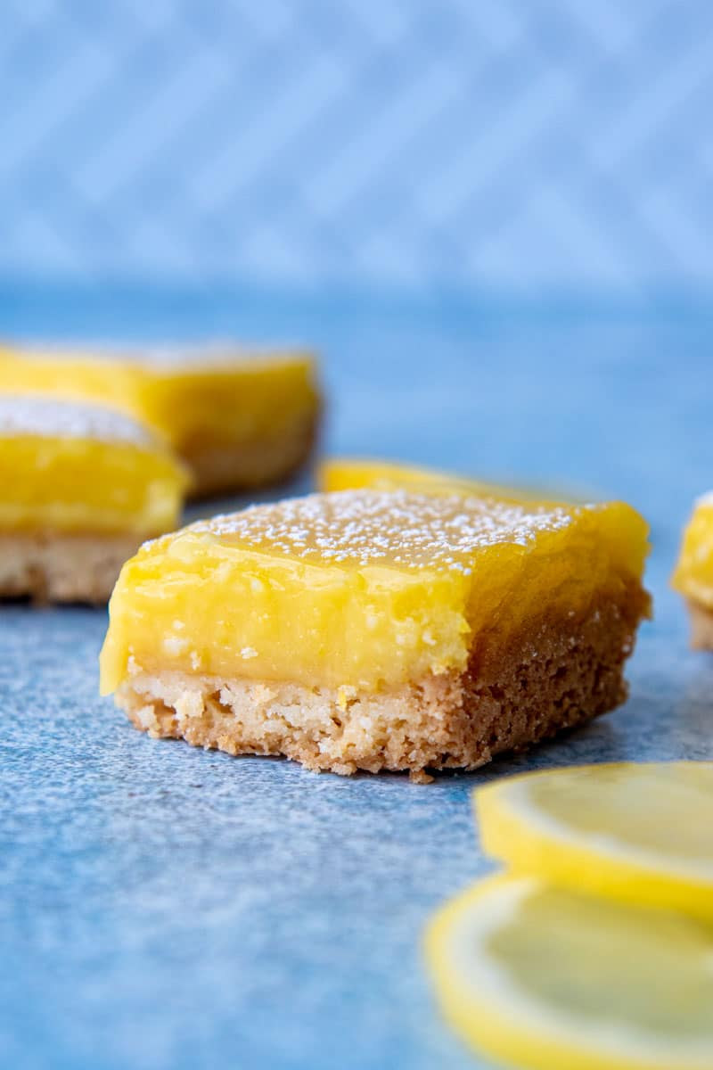 a cut gluten free lemon square on a blue board with more in the background
