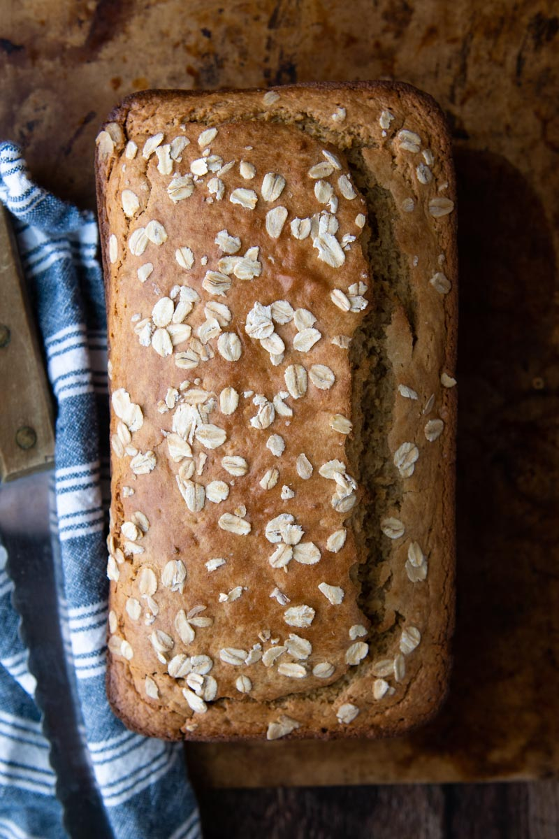 overhead shot of oat flour bread with oats sprinkled on top and a blue towel and knife next to it