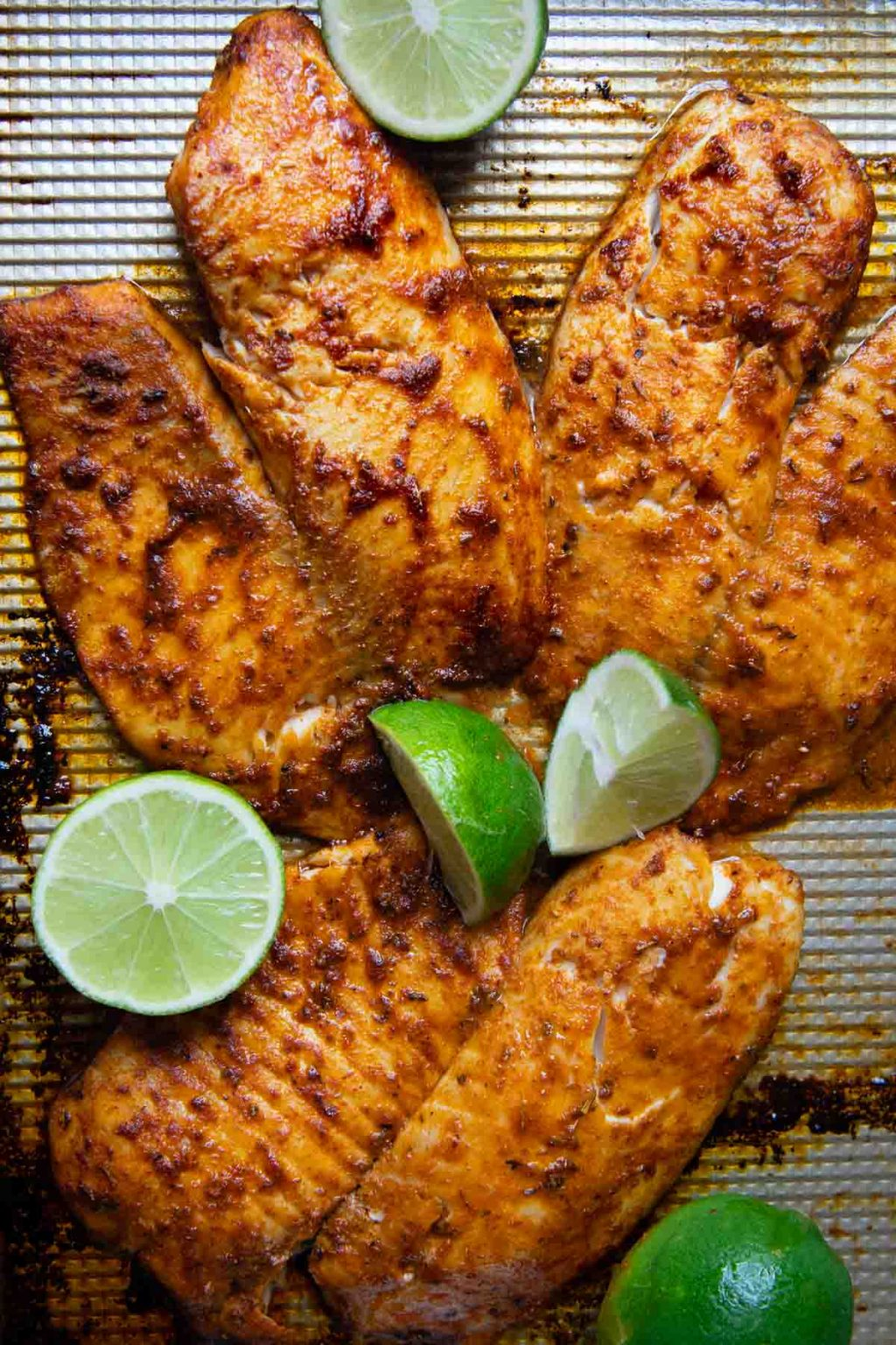 blackened seasoned fish on a baking sheet with limes