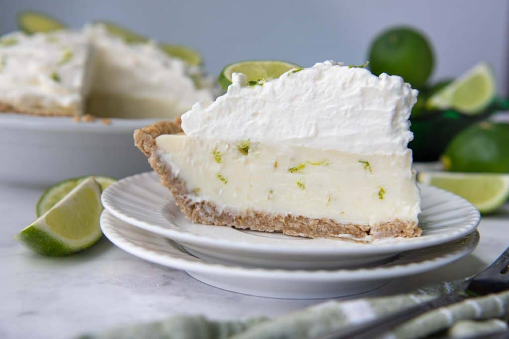 a slice of key lime pie on a white plate with whipped cream on top