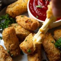a hand pulling the gluten free mozzarella sticks with cheese pulling out