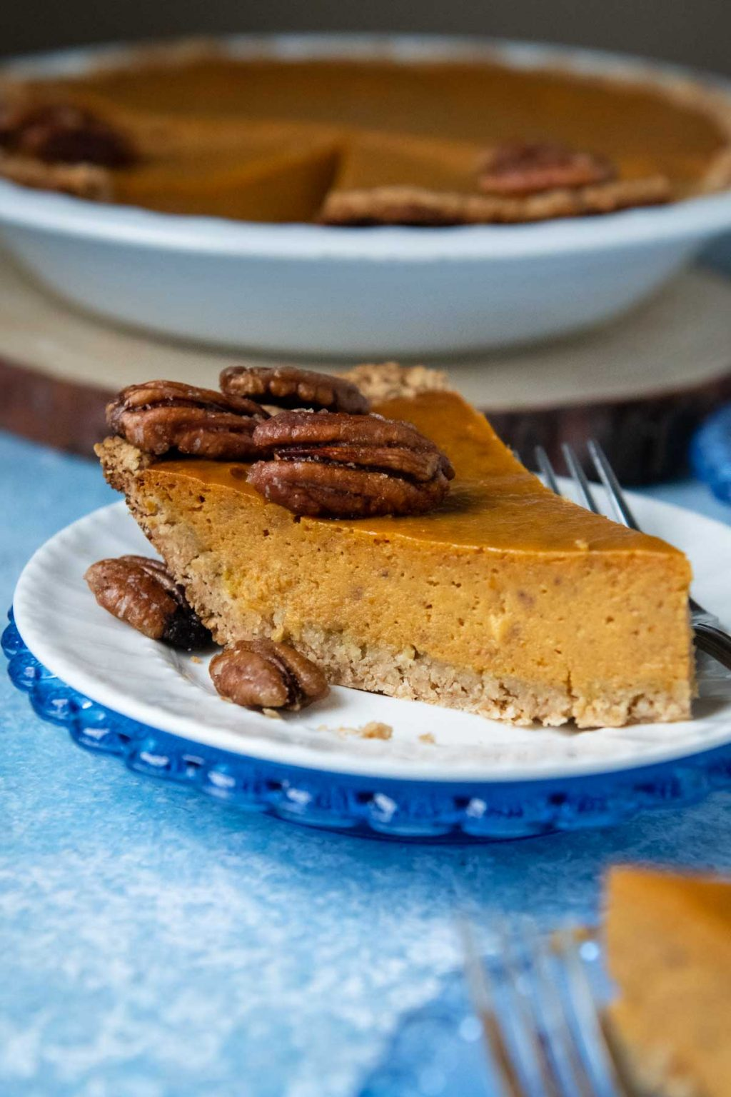 slice of pumpkin pie on a white plate on blue background