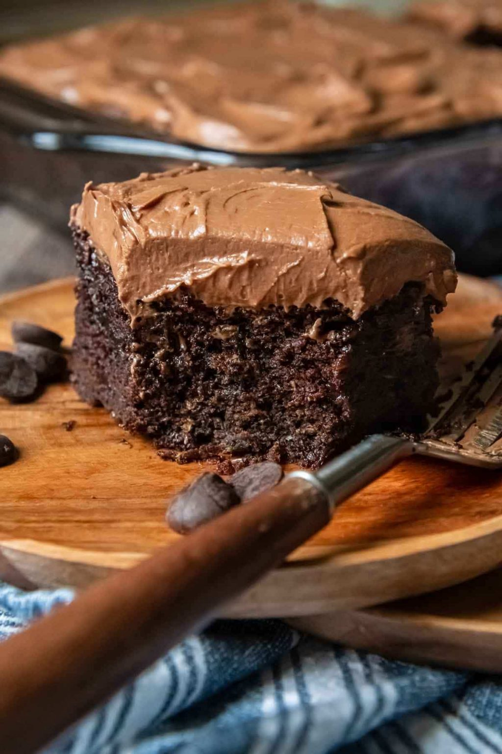 a slice of chocolate cake on a wood plate with a bite taken out