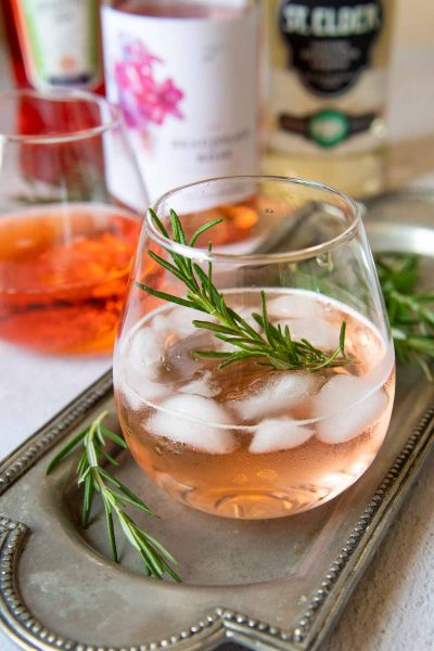 a rose spritz cocktail with bottles to make it in the background