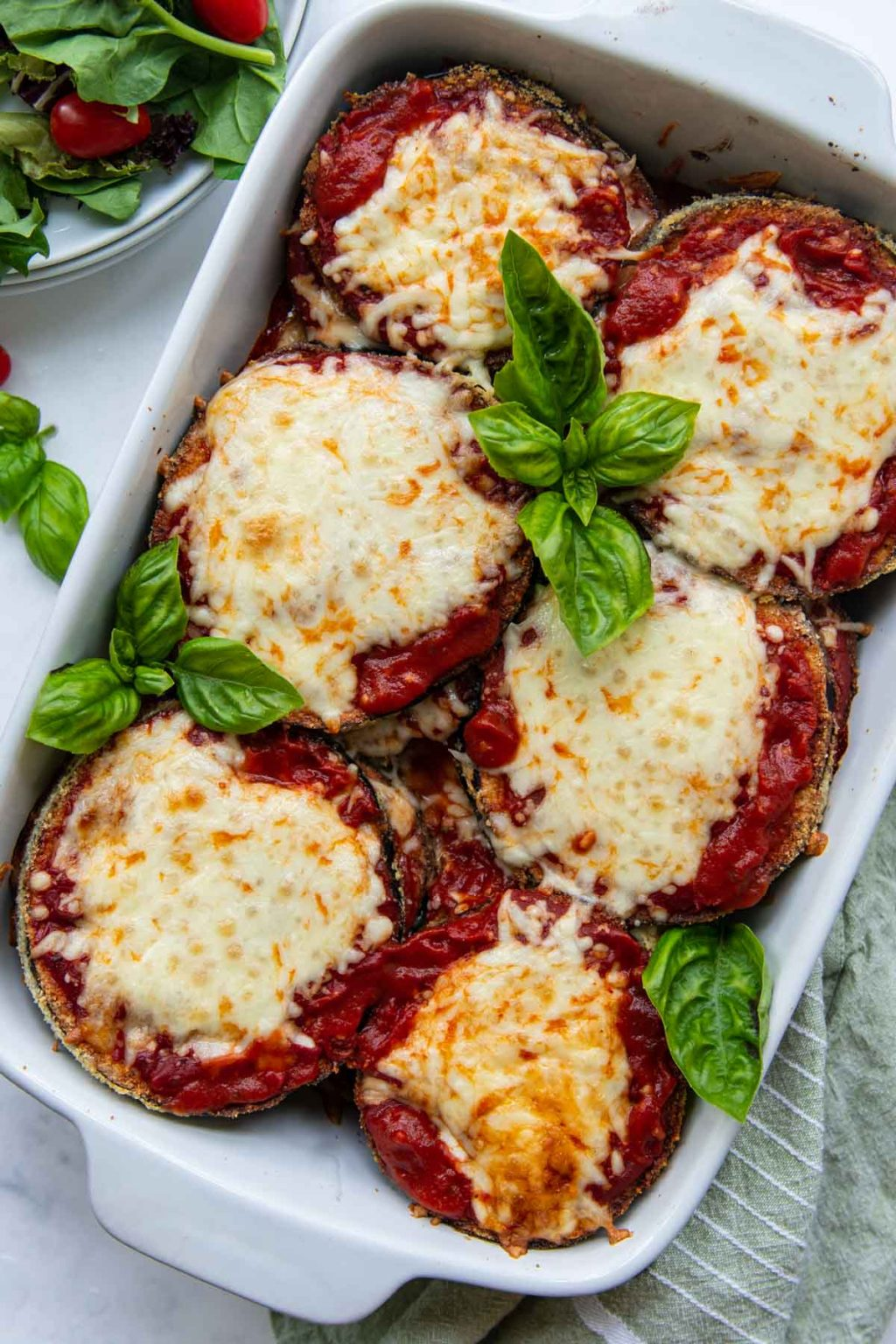 overhead shot of eggplant parmesan in a white baking dish with a salad next to it