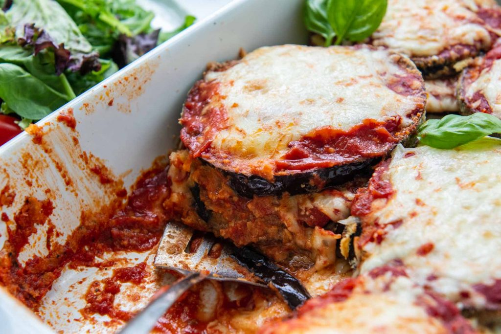 close up of low carb eggplant parmesan cut in a baking dish