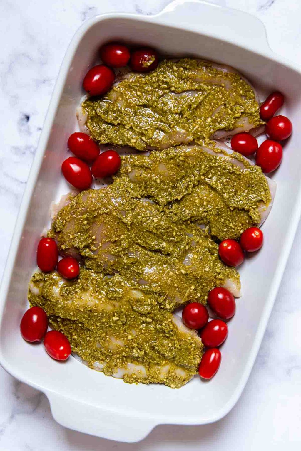 image showing pesto covered chicken with tomatoes around before it is baked