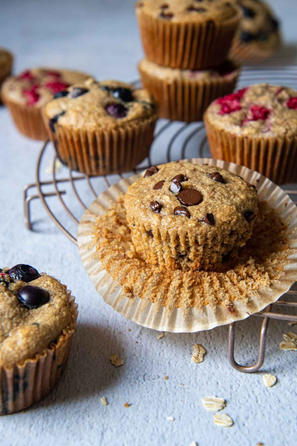 an unwrapped chocolate chip oat flour muffin on a cooling rack