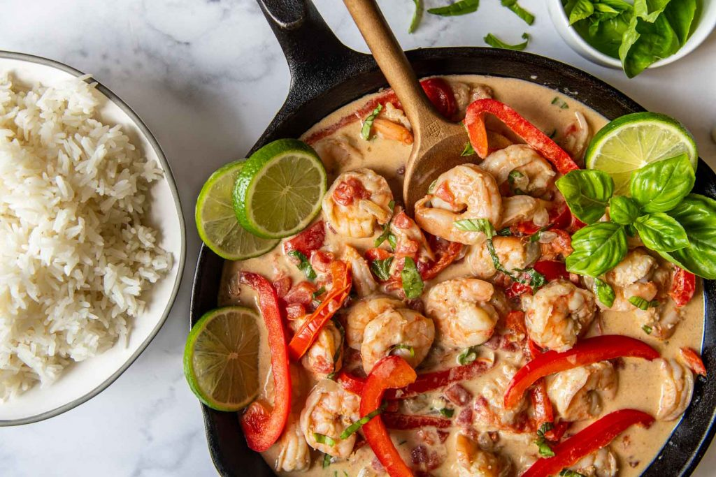 horizontal shot of creamy coconut shrimp in a black skillet with a bowl of rice next to it