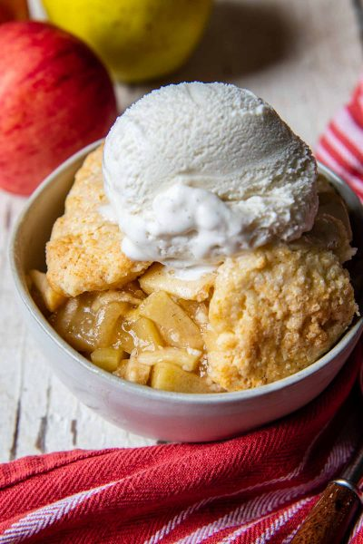 a serving of gluten-free apple cobbler in a white bowl with apples in the back ground