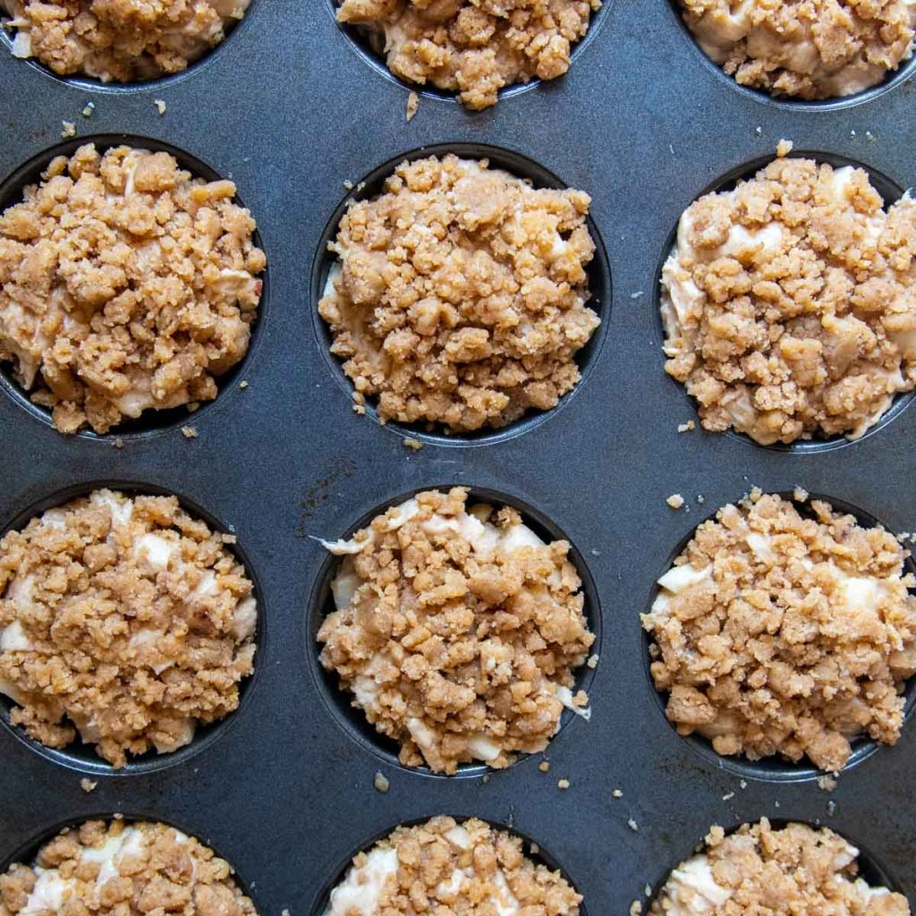 unbaked gluten-free apple muffins with streusel on top