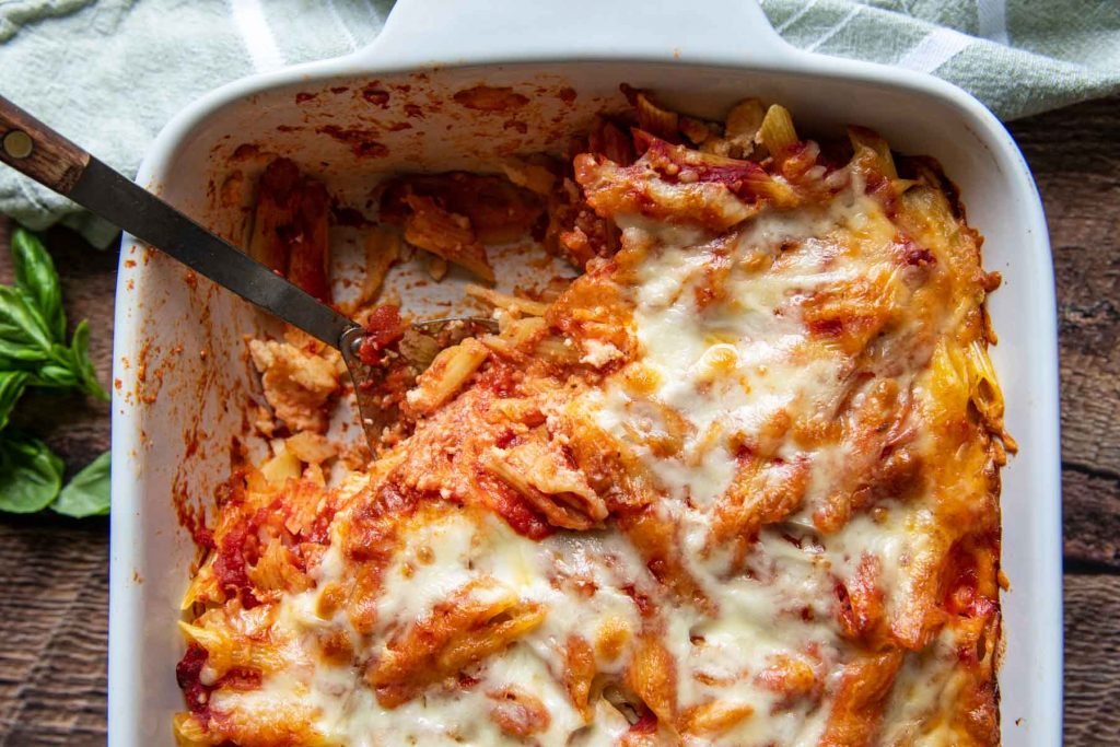 a spoon in a casserole dish of baked pasta with some taken out