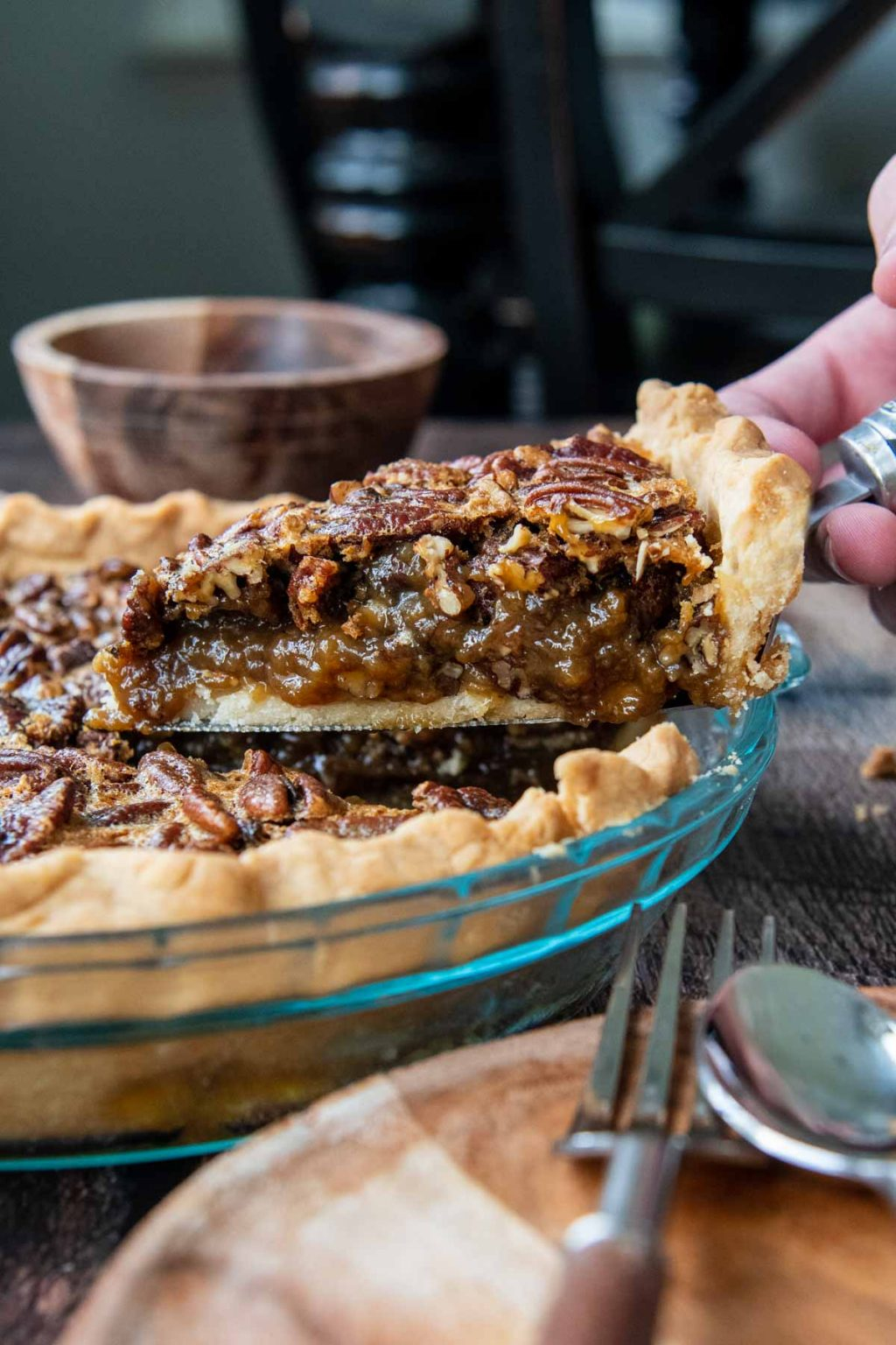 a piece of pecan pie being lifted out of a pie plate