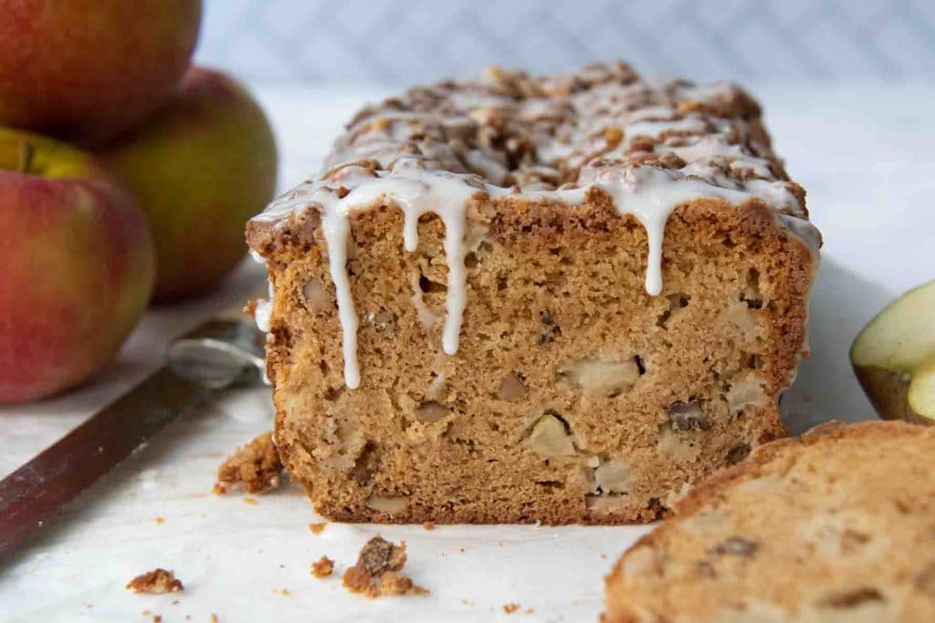 bread with frosting dripping down on cut loaf and apples stacked behind