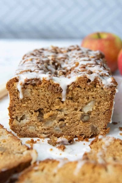 a cut apple bread with apples in the background and frosting dripping down